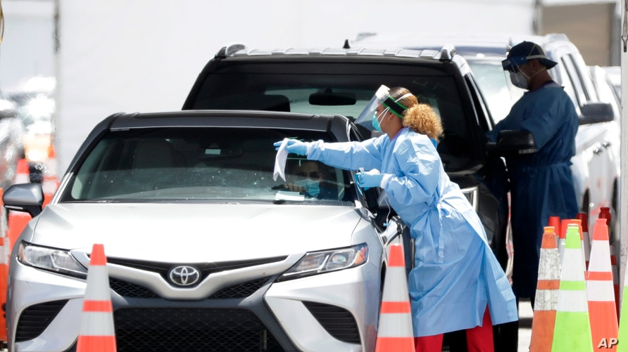 Healthcare workers prepare to test drivers at a drive-through coronavirus testing site outside of Hard Rock Stadium, June 26, 2020, in Miami Gardens, Florida.