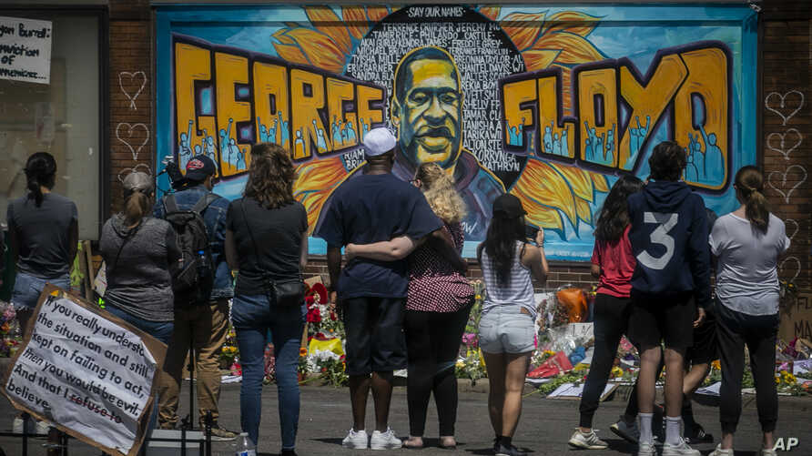FILE - People are seen gathered at a memorial featuring a mural of George Floyd, near the spot where he died while in police custody, in Minneapolis, Minnesota, May 31, 2020.