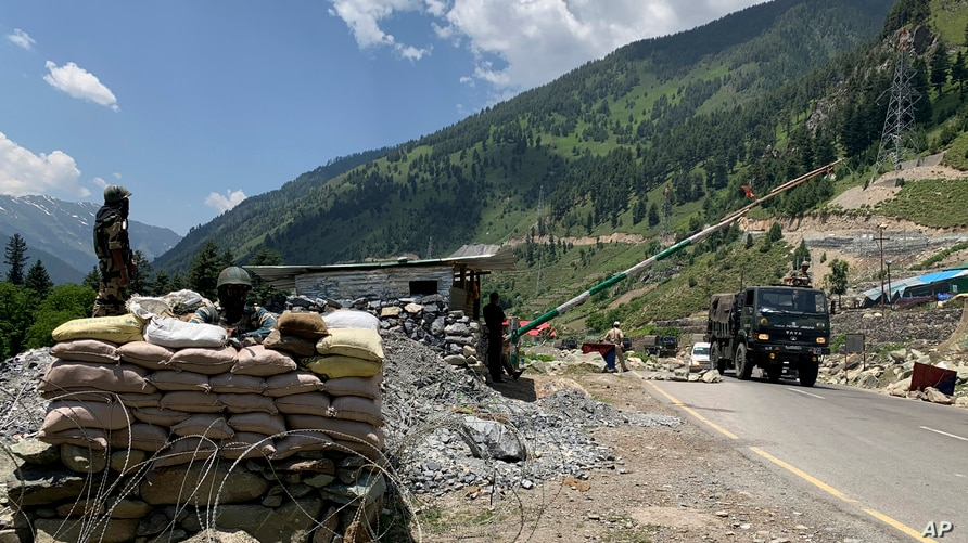 FILE - Indian paramilitary soldiers keep guard as an Indian army convoy moves along the Srinagar-Ladakh highway at Gagangeer, India, June 18, 2020, as a standoff between India and China over the Himalayan Galwan Valley escalates.