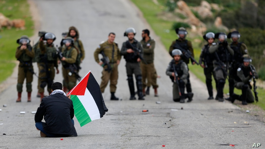 FILE - A demonstrator holds a Palestinian flag in front of Israeli forces as Palestinians protest against President Donald Trump's Mideast initiative, in Jordan Valley in the West Bank, Feb. 25, 2020.
