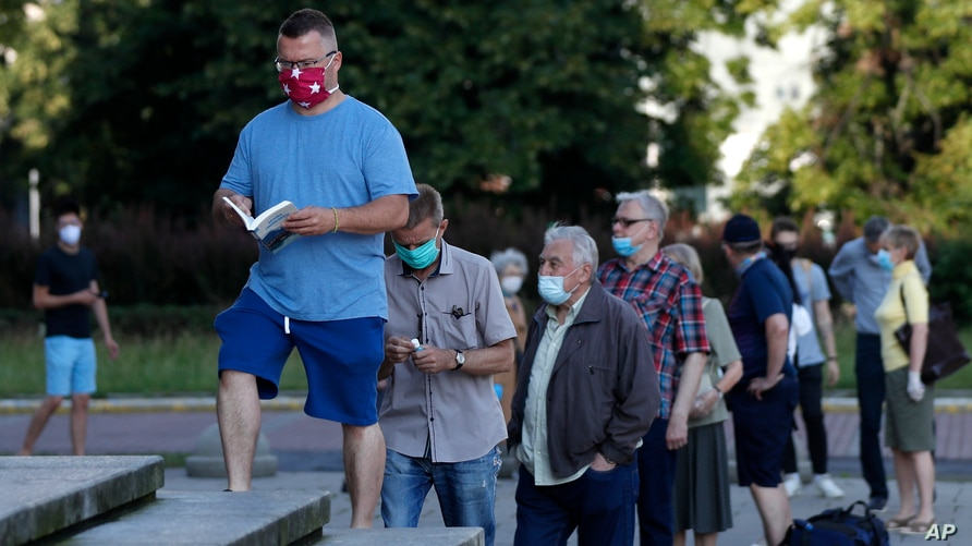 People, practicing social distancing, wait in line to cast their vote in presidential elections, in Warsaw, Poland, June 28, 2020.