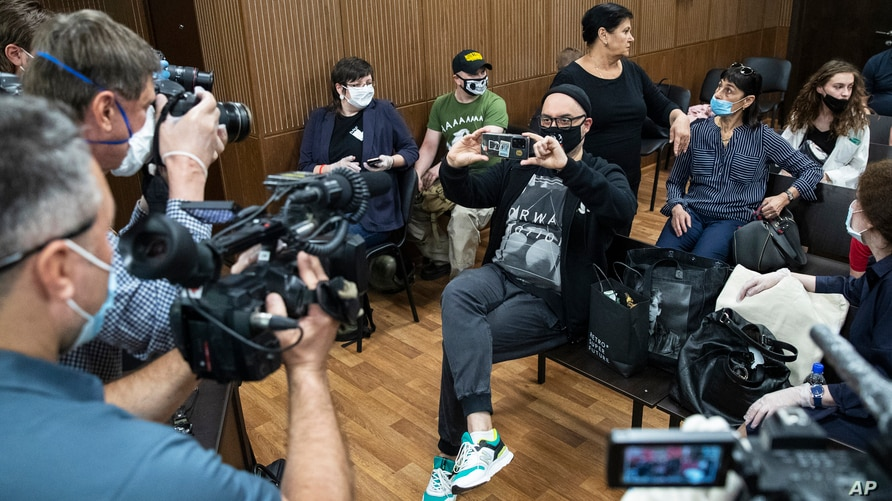 Russian theater and film director Kirill Serebrennikov, center, takes a photo of the media prior to his hearing in a court, in Moscow, Russia, June 22, 2020.