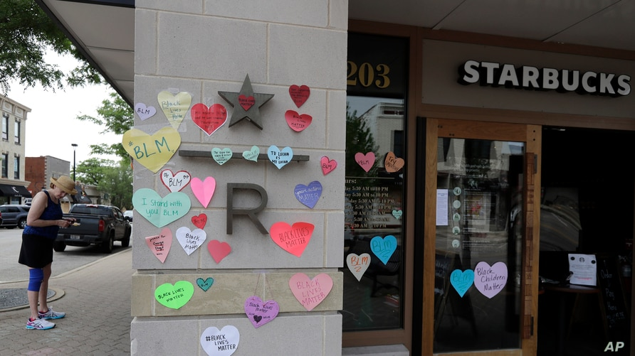 FILE - Hearts with messages in support of the Black Lives Matter movement are seen posted outside a Starbucks store in downtown Naperville, Illinois, June 4, 2020.