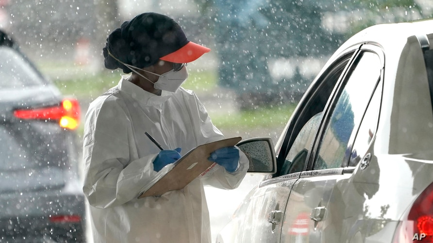 A healthcare worker takes down a patients information at a United Memorial Medical Center COVID-19 testing site, June 24, 2020, in Houston, Texas.