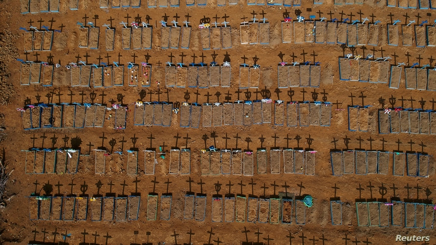FILE - An aerial view of crosses casting shadows at the Parque Taruma cemetery is seen amid the coronavirus pandemic, in Manaus, Brazil, June 15, 2020.