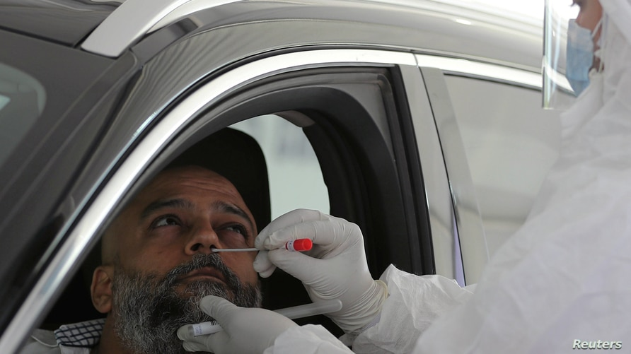 FILE - A health worker collects a sample at a drive-through COVID-19 screening center at the Ain Shams field hospital, in Cairo, Egypt, June 15, 2020.