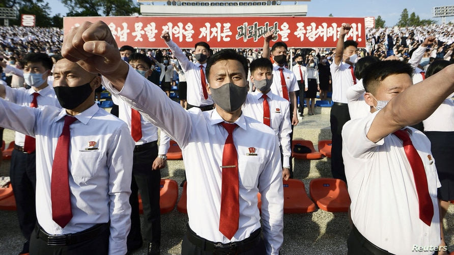 FILE - North Korean youth and students wearing protective face masks hold a rally condemning leaflets launched by defectors in South Korea with messages critical of Kim Jong Un's regime, in Pyongyang, North Korea, June 6, 2020. (Kyodo via Reuters)