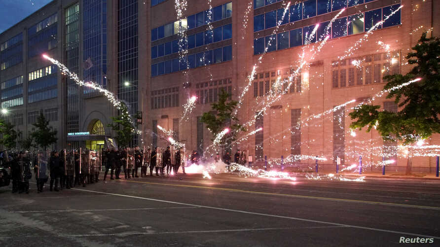 Fireworks explode near a group of law enforcement officers during a protest against the death in Minneapolis police custody of African-American George Floyd, in St Louis, Missouri, June 1, 2020.