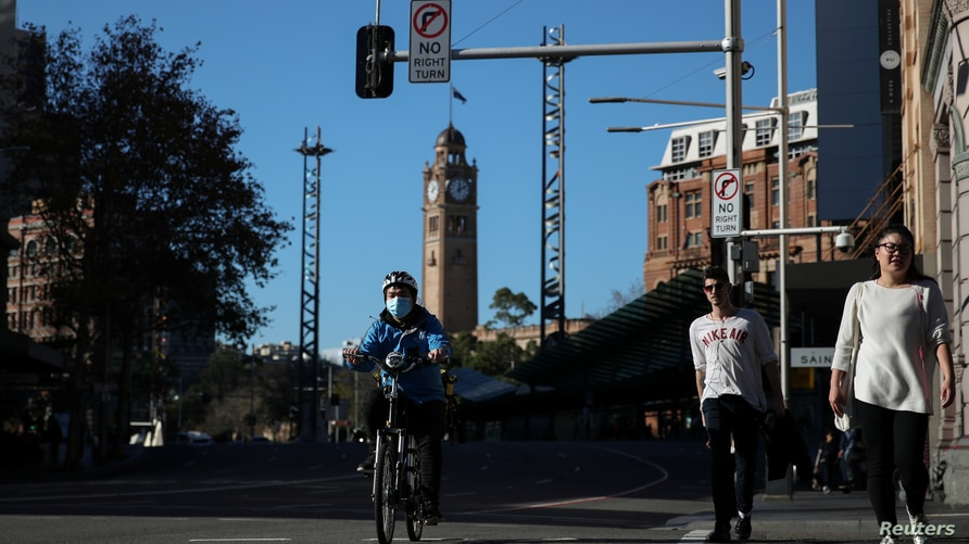 A bicycle delivery courier and pedestrians make their way through an intersection in the city center following the easing of restrictions implemented to curb the spread of the coronavirus disease (COVID-19) in Sydney, Australia, June 16, 2020.