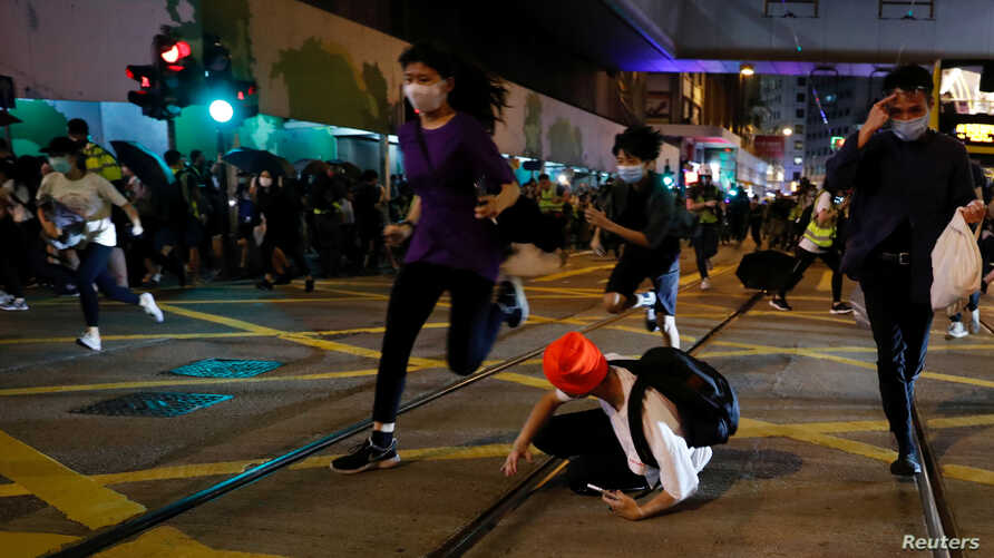 Pro-democracy demonstrators run away as riot police disperse them with pepper-spray pellet during a protest to mark first anniversary of a mass rally against a now-withdrawn extradition bill, in Hong Kong, China, June 9, 2020.