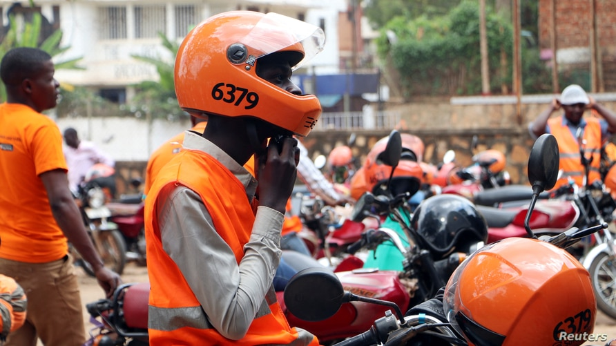 A motorcycle taxi driver known as boda-boda, from SafeBoda network, waits for a customer along a street in Kampala, Uganda, Oct. 5, 2018.