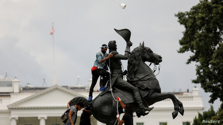 Protesters attach a chain to the statue of President Andrew Jackson to pull down in the middle of Lafayette Park outside the White House as someone throws a roll of toilet paper during racial inequality protests in Washington, D.C., June 22, 2020.