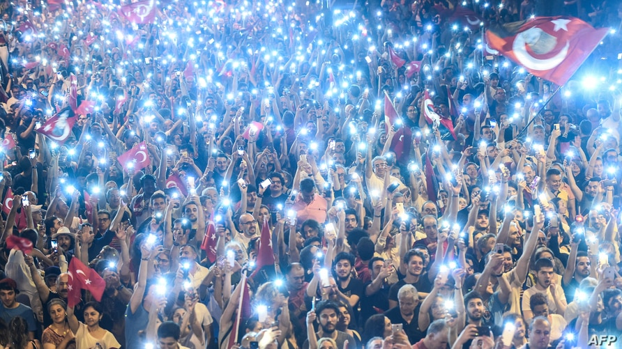 Supporters use flashlights on their cell-phones as they listen to presidential candidate of Turkey's main opposition Republican…