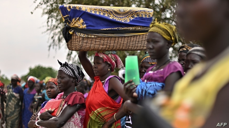 A woman balances a reed basket bearing her child on her head as she stands with fellow villagers in systemic queues as they…