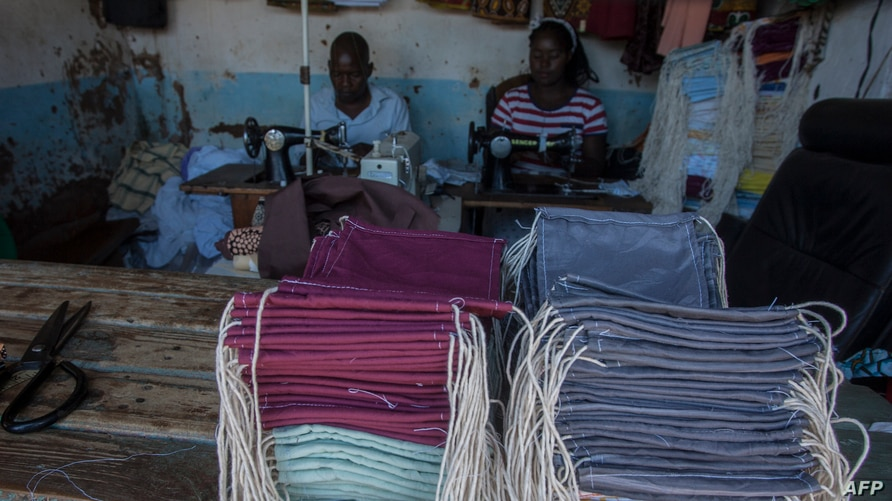 Amos Banda (L) and Agatha Mbamba, tailors, make facemasks at the Tayamba Tailoring shop which has embarked in the business of…