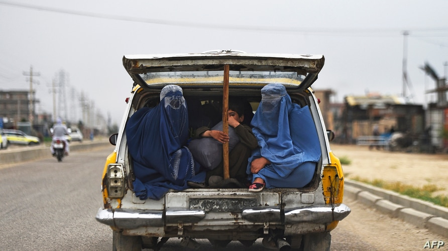 In this photo taken on May 13, 2020, Afghan women and a boy travel in a taxi car on the outskirts of Mazar-i-Sharif. (Photo by…