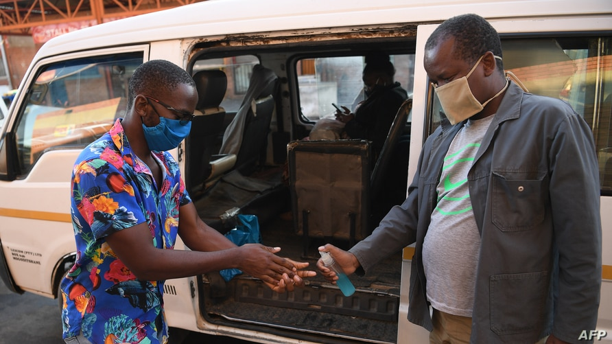 A man receives hand sanitiser as a preventive measure against the spread of the COVID-19 coronavirus before boarding a taxi in…