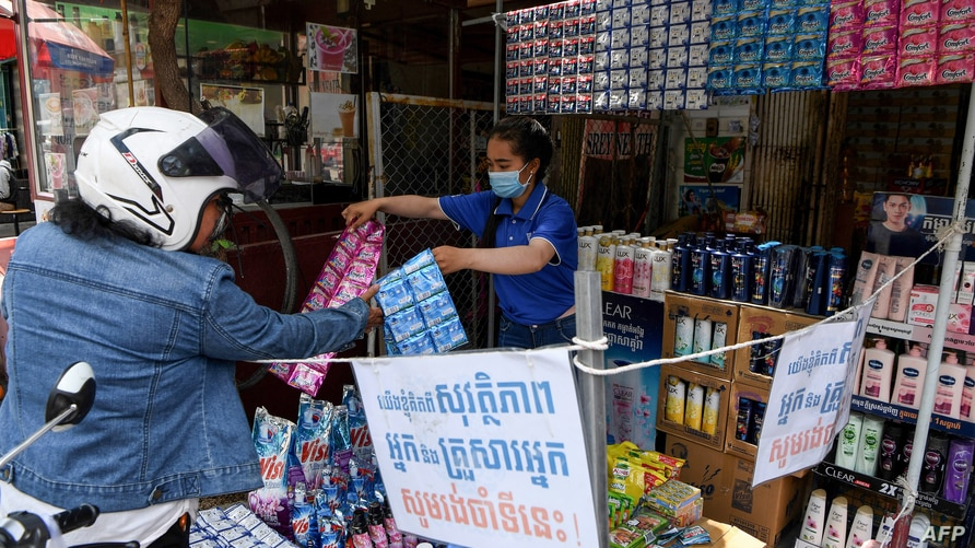 A vendor shows sachets of hair shampoo to a customer from a shop that has been marked off to allow for social distancing, as a…