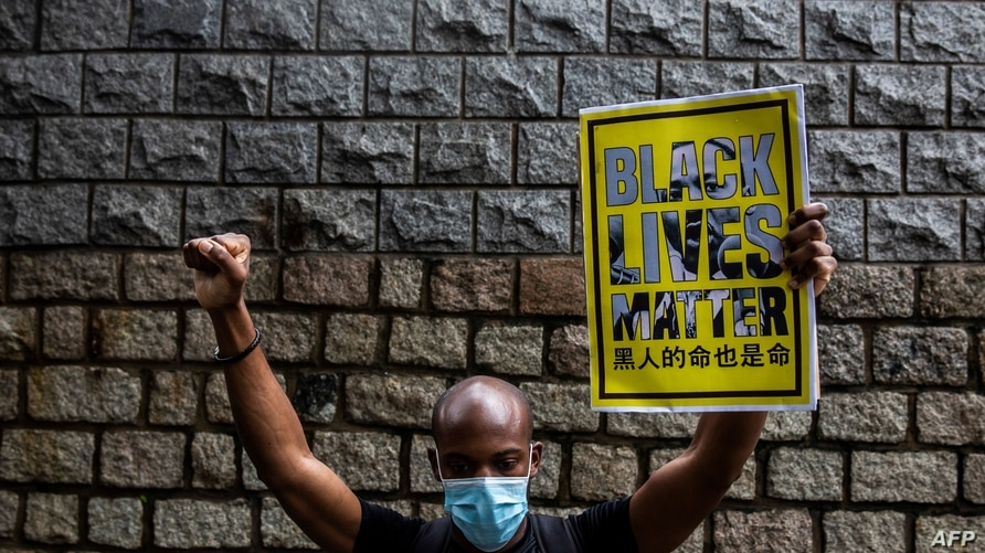 A protester holds a Black Lives Matter sign outside the US consulate during a demonstration against racism and police brutality…