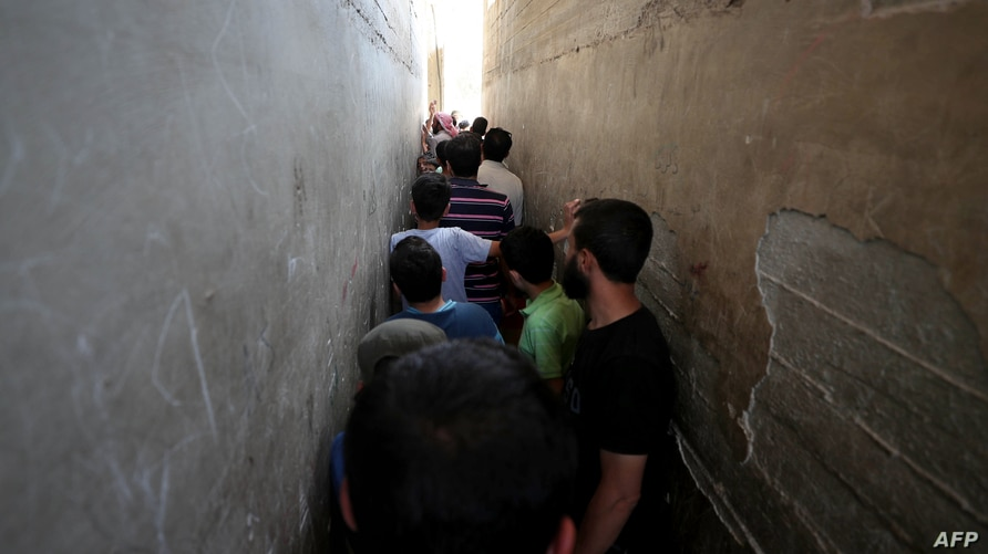 Syrians line up to buy bread at a shop in the town of Binnish in the country's northwestern Idlib province on June 9, 2020. -…