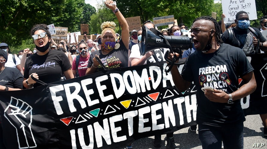 Demonstrators take part in a Juneteenth march and rally in Downtown Washington, DC, on June 19, 2020. - The US marks the end of…