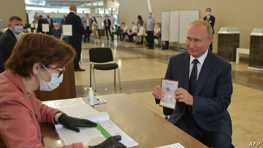 Russian President Vladimir Putin shows his passport to a member of a local electoral commission as he arrives to cast his…