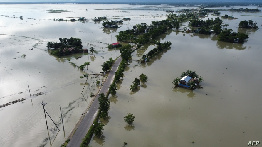 In this aerial photo inundated houses are seen in Sunamgong on July 14, 2020. - Almost four million people have been hit by…
