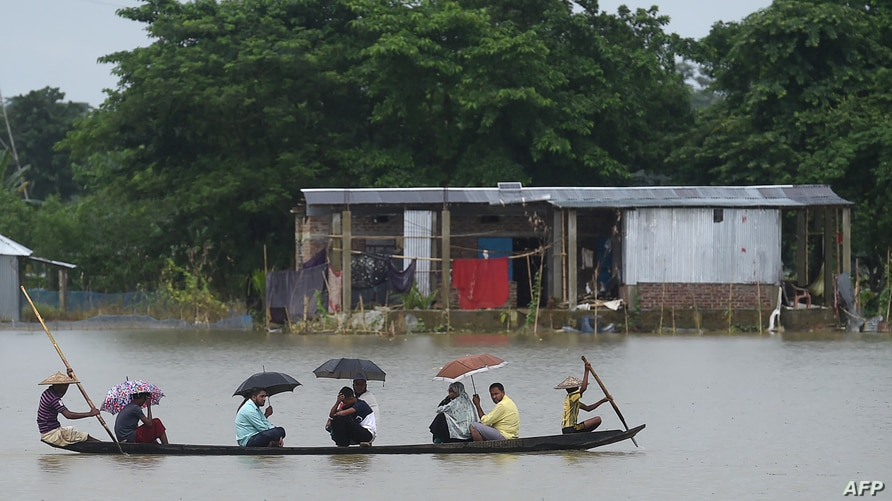 People ride on a boat through flooded waters in Sunamgong on July 14, 2020. - Almost four million people have been hit by…