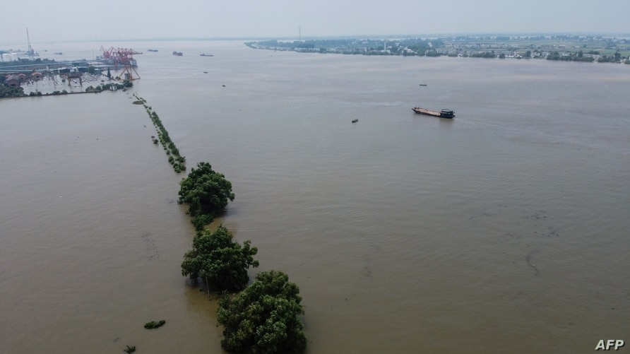 An aerial view shows the swollen Yangtze river in Jiujiang, in China's central Jiangxi province on July 17, 2020. - Heavy rains…
