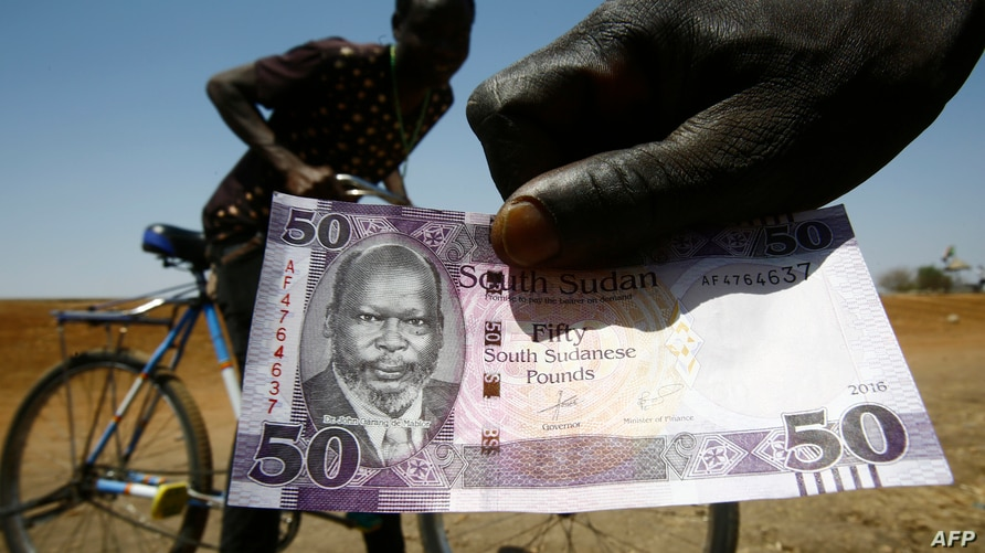A South Sudanese refugee shows his country's fifty-pound note as he flees across the border in Sudan's White Nile state on…