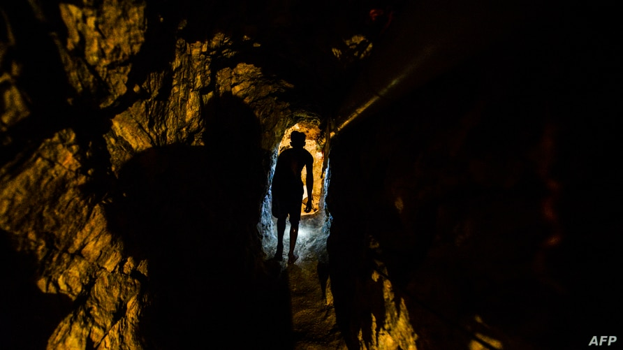 A man walks in a tunnel at a gold mine in El Callao, Bolivar state, southeastern Venezuela on March 1, 2017. - Although life in…