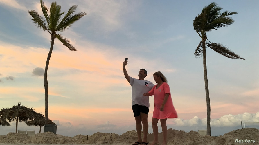 A couple videochats on their smartphone on the beach in the aftermath of Hurricane Matthew near Nassau, Bahamas October 9, 2016…