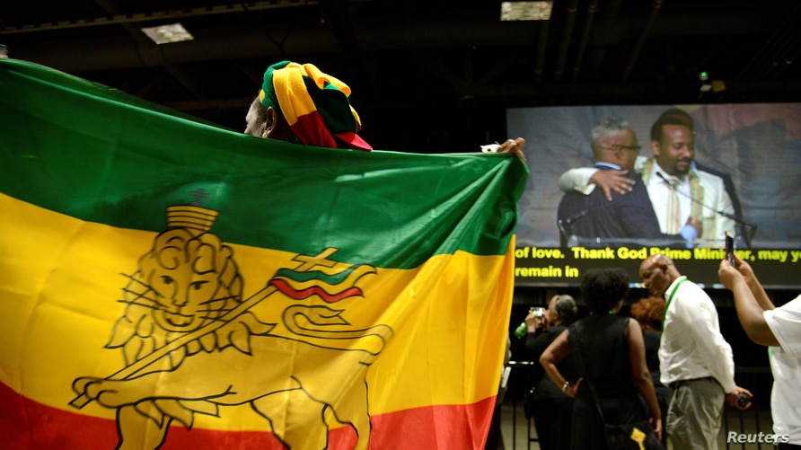 A member of the Ethiopian diaspora, the largest outside of Ethiopia, holds a national flag as Ethiopia's Prime Minister Abiy…