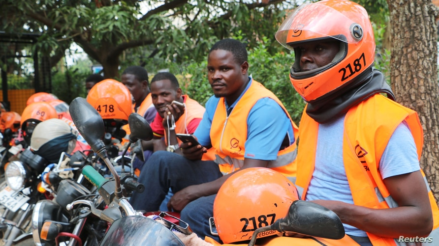 Motorcycle taxi drivers known as boda-boda, wear SafeBoda safety gear as they wait for customers along a street in Kampala,…