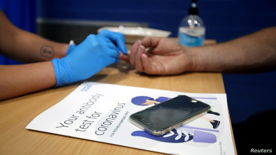 A man has his finger pricked during a clinical trial of tests for the coronavirus disease (COVID-19) antibodies, at Keele…