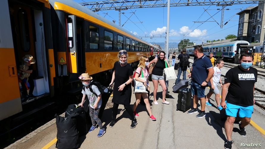 FILE - Tourists exit a train on the first direct train service from Prague to Rijeka, at the station in Rijeka, Croatia, July 1, 2020.