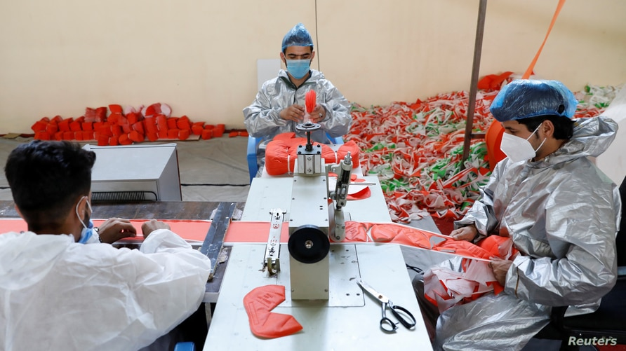 Men wear protective face mask as they work at a mask factory, during the coronavirus disease (COVID-19) outbreak in Kabul,…