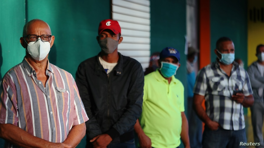 People wearing protective masks stand in line to cast their votes in the general election during the outbreak of the…