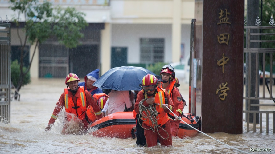 Rescue workers evacuate with an inflatable boat students stranded by floodwaters at a school, amid heavy rainfall in Duchang county, Jiangxi province, China July 8, 2020.