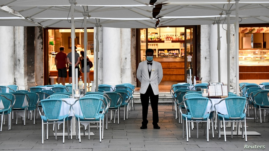 A bar employee wears a protective face mask while standing at St. Mark's Square amid the coronavirus disease (COVID-19)…