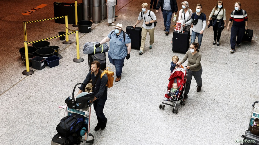 Passengers wearing face masks walk at the Helsinki-Vantaa airport in Vantaa, as Finnish Government has eased travel…