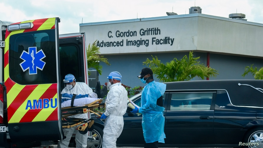 Emergency Medical Technicians (EMT) arrive with a patient while a funeral car begins to depart at North Shore Medical Center…