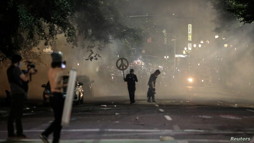 Demonstrators return to protest against racial inequality in front of federal buildings despite lingering tear gas fired by…
