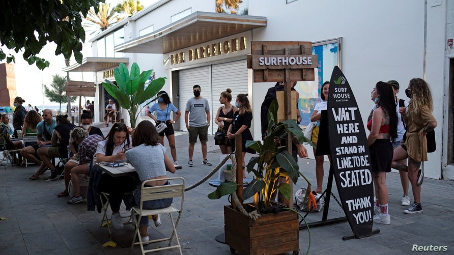 FILE PHOTO: People sit at a bar near Barceloneta beach, after Catalonia's regional authorities and the city council announced…