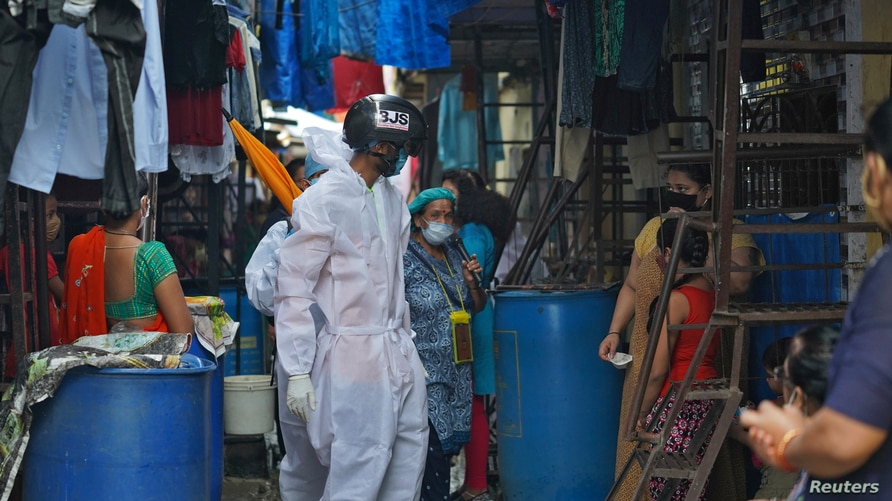 A worker wearing a 'Smart Helmet' thermoscanner that measures the temperature of people at a distance, screens residents in a slum Mumbai, India, July 23, 2020.
