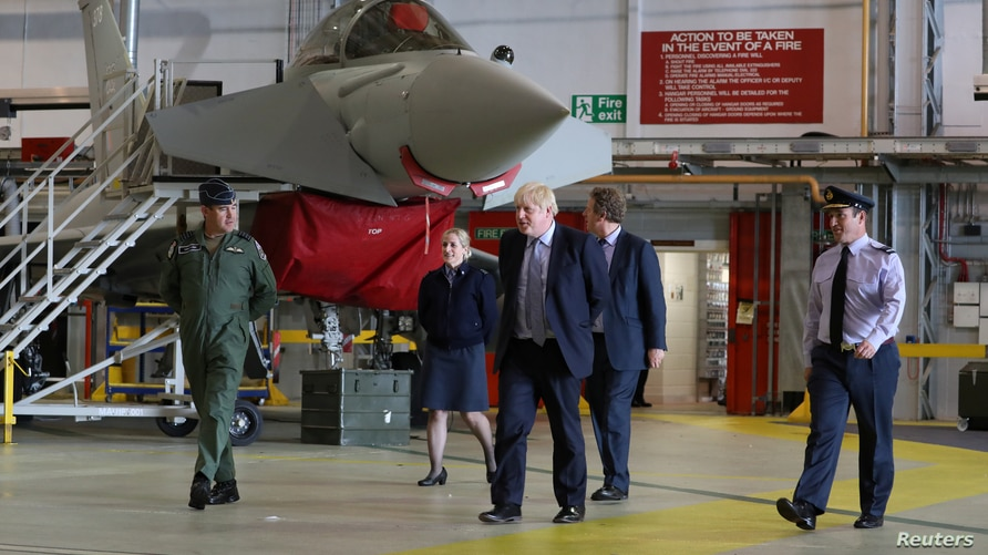 Britain's Prime Minister Boris Johnson walks next to a Typhoon fighter jet at RAF Lossiemouth, during a visit to the Highlands…