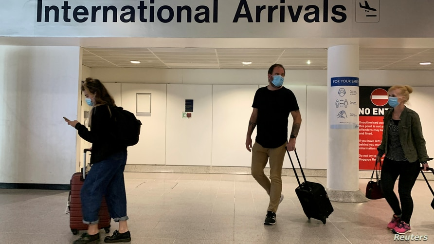 Passengers are seen wearing face coverings after arriving at Manchester Airport following the outbreak of the coronavirus…