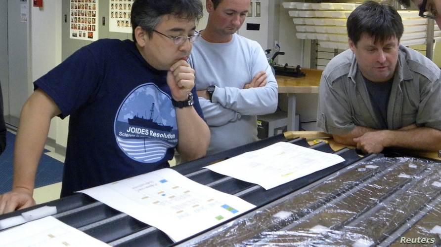 Researchers Yuki Morono, Laurent Toffin and Steven DÕHondt (L-R) work aboard the research drillship JOIDES Resolution with…