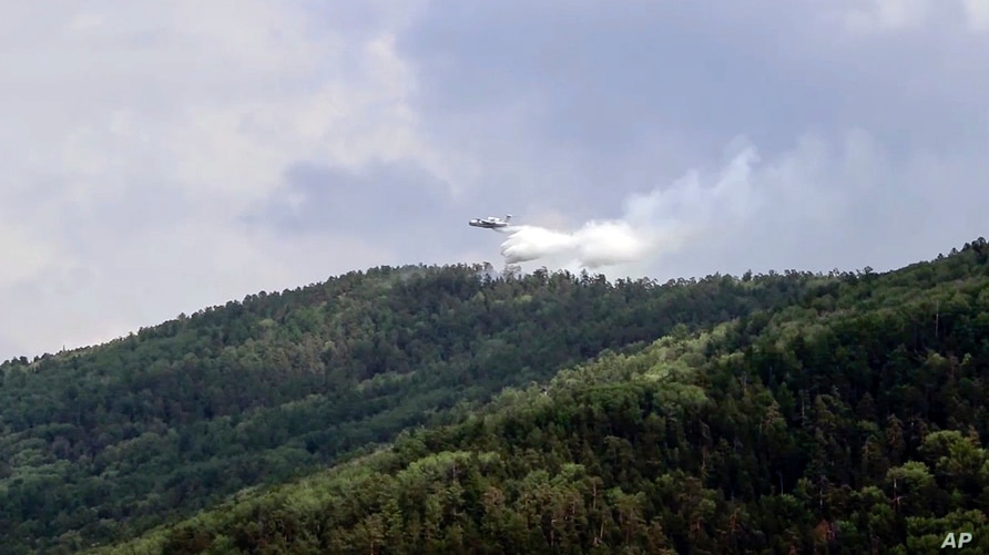 A grab from video provided by Russian Emergency Ministry, shows a Russian Emergency Ministry's Beriev plane BE-200 Be-200 multipurpose amphibious aircraft releasing water in the Trans-Baikal National Park in Buryatia, southern Siberia, July 10, 2020.