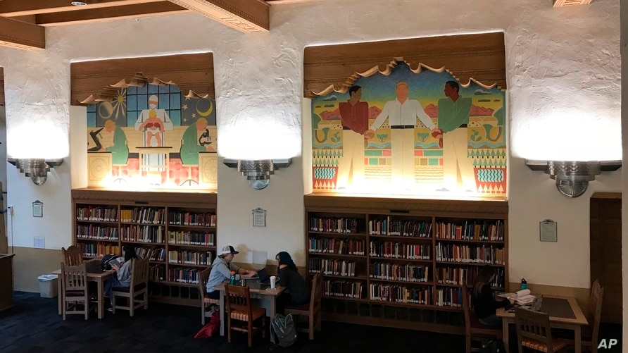 Students study below a series of murals in the west wing of the University of New Mexico's historic Zimmerman Library in…